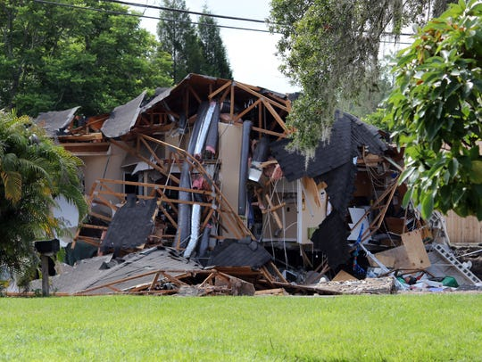 Debris is strewn about from a partially collapsed home