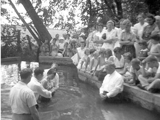 This 1956 photograph shows a baptism in progress at