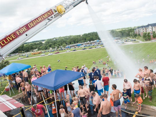 The Clive Fire Department pump truck keeps the water flowing down the giant slip 'n slide at the 2015 Clive Festival.