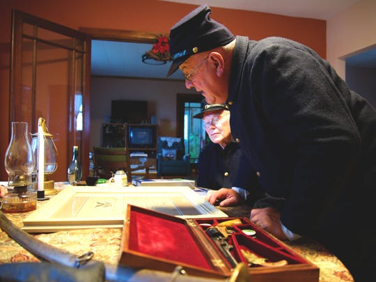 Roy Luebke and Gerald Neuser look over a document signed by President Abraham Lincoln and other Civil War ear memorabilia.