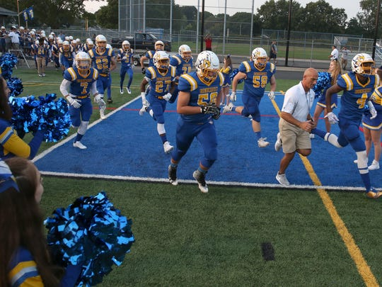 Irondequoit players race onto the field through a tunnel of their supporting cheerleaders as they take the field for their first home game of the season against Canandaigua.