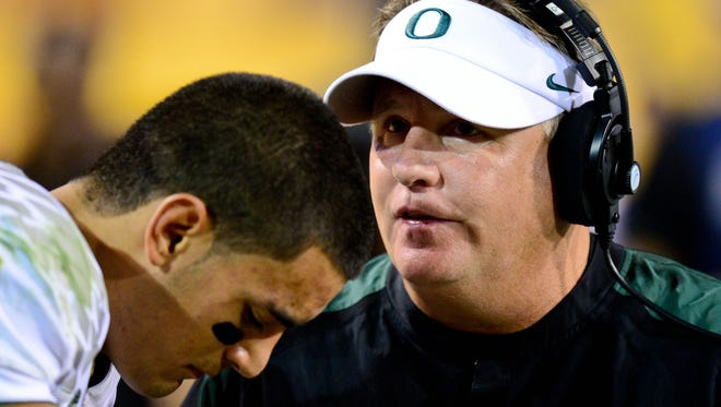 Then-Oregon coach Chip Kelly talks with quarterback Marcus Mariota in 2012.