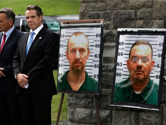 Peter Shumlin, Andrew Cuomo next to pictures of prisoners who escaped.