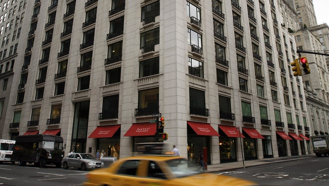 A taxi cab passes in front of Barneys New York on Madison Avenue in midtown Manhattan.