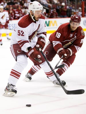 Coyotes forward Justin Hodgman (52) controls the puck in front of Coyotes forward Shane Doan during the first period of an intra-squad scrimmage at Gila River Arena in Glendale on Saturday, September 27, 2014.