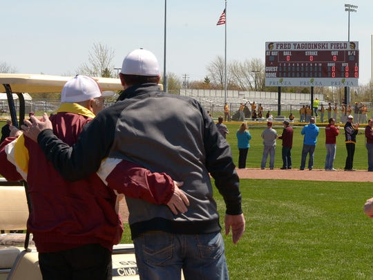 "Fred Yagodinski (left) and his son, Dan, embrace after the unveiling of the name plate ""Fred Yagodinski Field"" on the scoreboard at the baseball diamond at Luxemburg on Saturday."