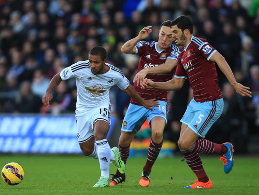 Swansea City's Wayne Routledge, left, battles past West Ham United's Mark Noble, center, and James Tomkins during their English Premier League match at the Liberty Stadium, Swansea, Wales, Saturday, Jan. 10, 2014. (AP Photo/Nick Potts, PA Wire)      UNITED KINGDOM OUT     -   NO SALES    -    NO ARCHIVES