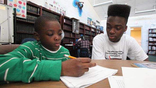 Spring Valley High School senior Florby Dorme helps Arlee Senat, 9, with his homework as part of the after-school program at the Martin Luther King Multi-Purpose Center in Spring Valley.