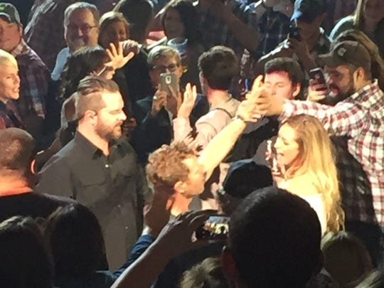 Dierks Bentley high fives fans as he makes his away