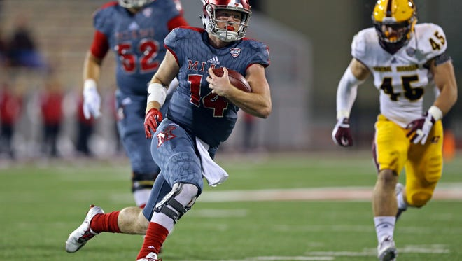 Miami RedHawks quarterback Gus Ragland (14) carries the ball against the Central Michigan Chippewas in the first half at Fred Yager Stadium.