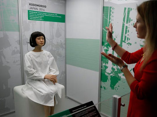A member of the media tries to attract the attention of Kodomoroid a life like Japanese robot, which is a designed robotic news reader for the Miraikan the Japanese national Museum of Emerging Science and Innovation, during a press preview for the Robots exhibition held at the Science Museum in London, Tuesday, Feb. 7, 2017. The exhibition which shows 500 years of mechanical and robotic advances is open to the public form Feb. 8 through to Sept. 3.
