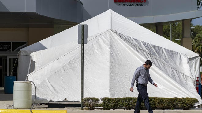 A healthcare employee walks by two tents being set up outside the ER that will eventually be used to screen patients at Boca Raton Regional Hospital in Boca Raton, Florida on  March 18, 2020.