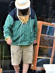 Vernon Britton uses a bee smoker to calm the bees while