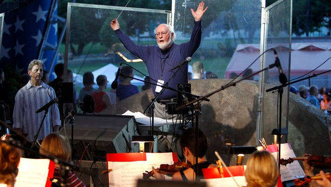 John Williams conducts the National Symphony Orchestra and other musicians for the upcoming debut of a new arrangement of the national anthem on Capitol Hill in Washington on July 2, 2014. It will be performed July 4 on the National Mall before the annual fireworks show.