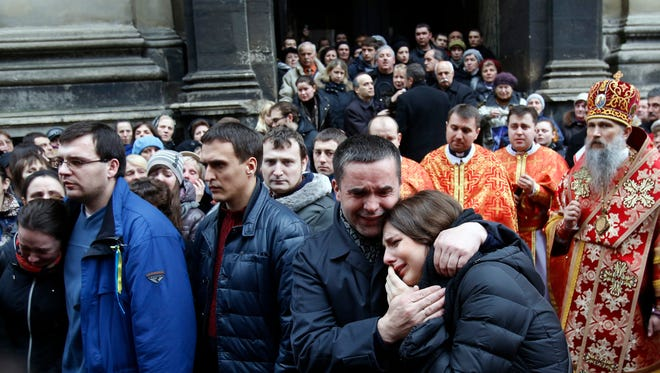 People react during a service of Bogdan Solchunuk, in front of the St. Paul and Peter church in Lviv, western Ukraine Saturday. Church services were held Saturday in the pro-opposition stronghold of Lviv in the west of Ukraine for the locals who were killed in Kiev during the past week.