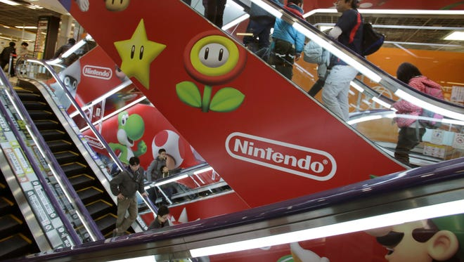 Shoppers take escalators painted with the logos of Nintendo and Super Mario characters at an electronics store in Tokyo. Nintendo Co. sank to a worse-than-expected loss for the fiscal first quarter on lagging Wii U and 3DS video-game machine sales. But the Japanese company behind Super Mario and Pokemon games stuck to its annual forecasts Wednesday, July 30, 2014 for a 20 billion yen ($196 million) profit on 590 billion yen ($5.8 billion) sales.