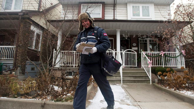 A Canada Post employee delivers mail and parcels to residential homes in Toronto on Wednesday.