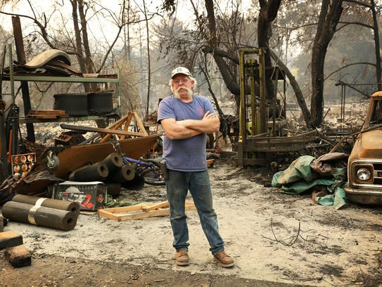 Rick Dunham poses for a portrait on his fire damaged
