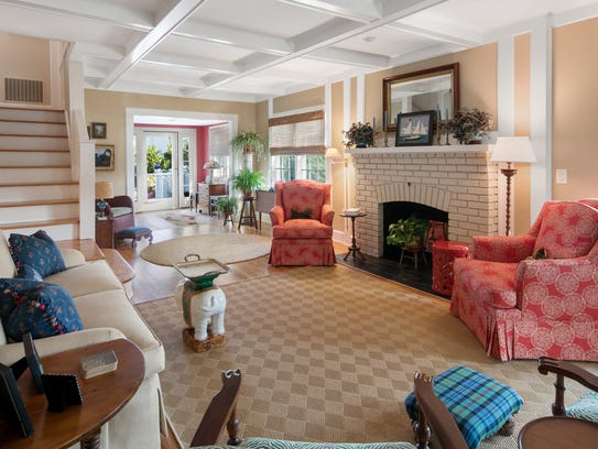 A spacious living room with wood burning fireplace and decorative ceilings.