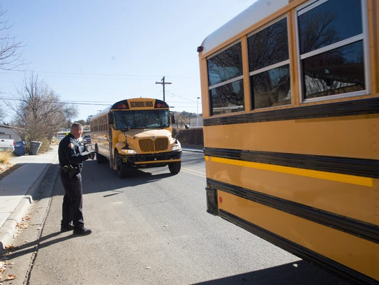 A Bloomfield Police officer directs schools buses containing