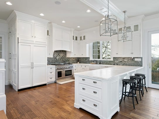 The all-white kitchen features stainless steel appliances and custom lighting.