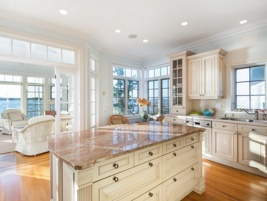 The eat-in kitchen has custom cabinetry and a center
