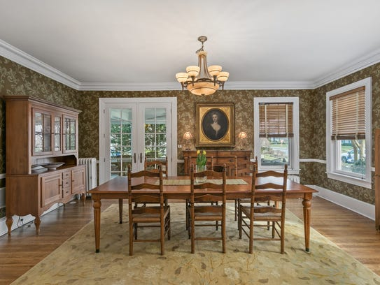 The dining room features a stylistically wallpaper and a set of elegant paned glass French Doors.