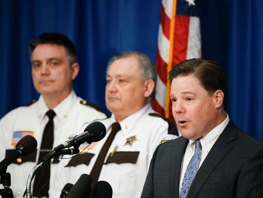 Carver County Attorney Mark Metz, right, and flanked