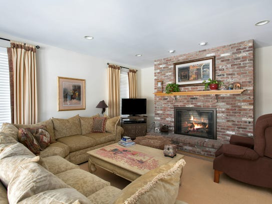 The family room features a gracious large masonry fireplace and recessed lighting.