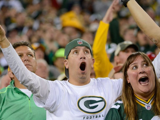 Packers fans react to a call by referees in a game