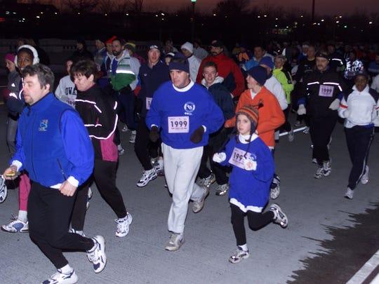 Runners start the 30th Annual New Year's Eve Belle Isle Family Fun Run/Walk on Friday night, Dec. 31, 1999.