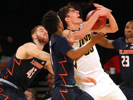 Iowa Hawkeyes forward Luka Garza (55) grabs a rebound against Illinois Fighting Illini forward Michael Finke (43) and guard Trent Frazier (1) and guard Aaron Jordan (23) during the second half of a first round game of the 2018 Big Ten Tournament at Madison Square Garden.
