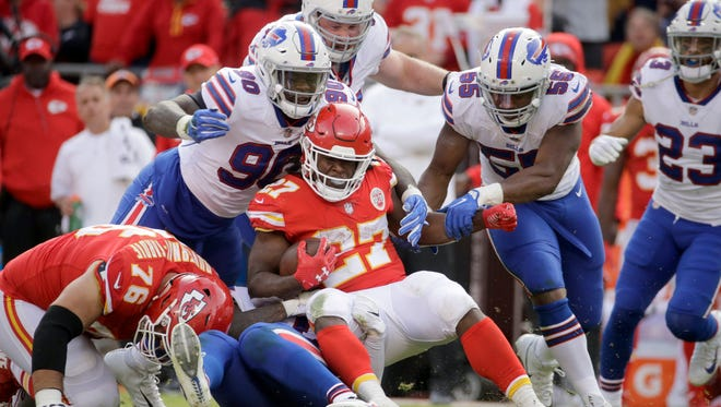 Kansas City Chiefs running back Kareem Hunt (27) is tackled by Buffalo Bills defensive end Shaq Lawson (90), defensive tackle Kyle Williams, top, and defensive end Jerry Hughes (55) during the second half of an NFL football game in Kansas City, Mo., Sunday, Nov. 26, 2017. (AP Photo/Charlie Riedel)