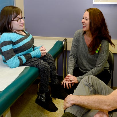 Anna Grace Wright, 14, and her mother Judy speak with Dr. Pete Stasikelis at Shriners Hospital for Children on Wednesday.