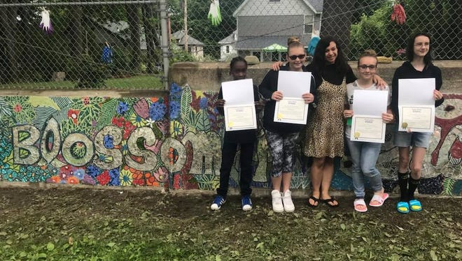 Emily Jablon (center) worked with students at West Middle School to create a mosaic for the school's garden.