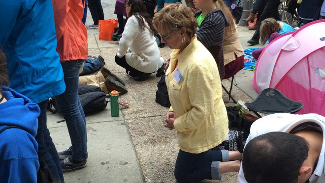 Sharon Guernsey of Lapeer, Mich., kneels on the sidewalk during the Papal Mass in Philadelphia on Sunday, Sept. 27, 2015.