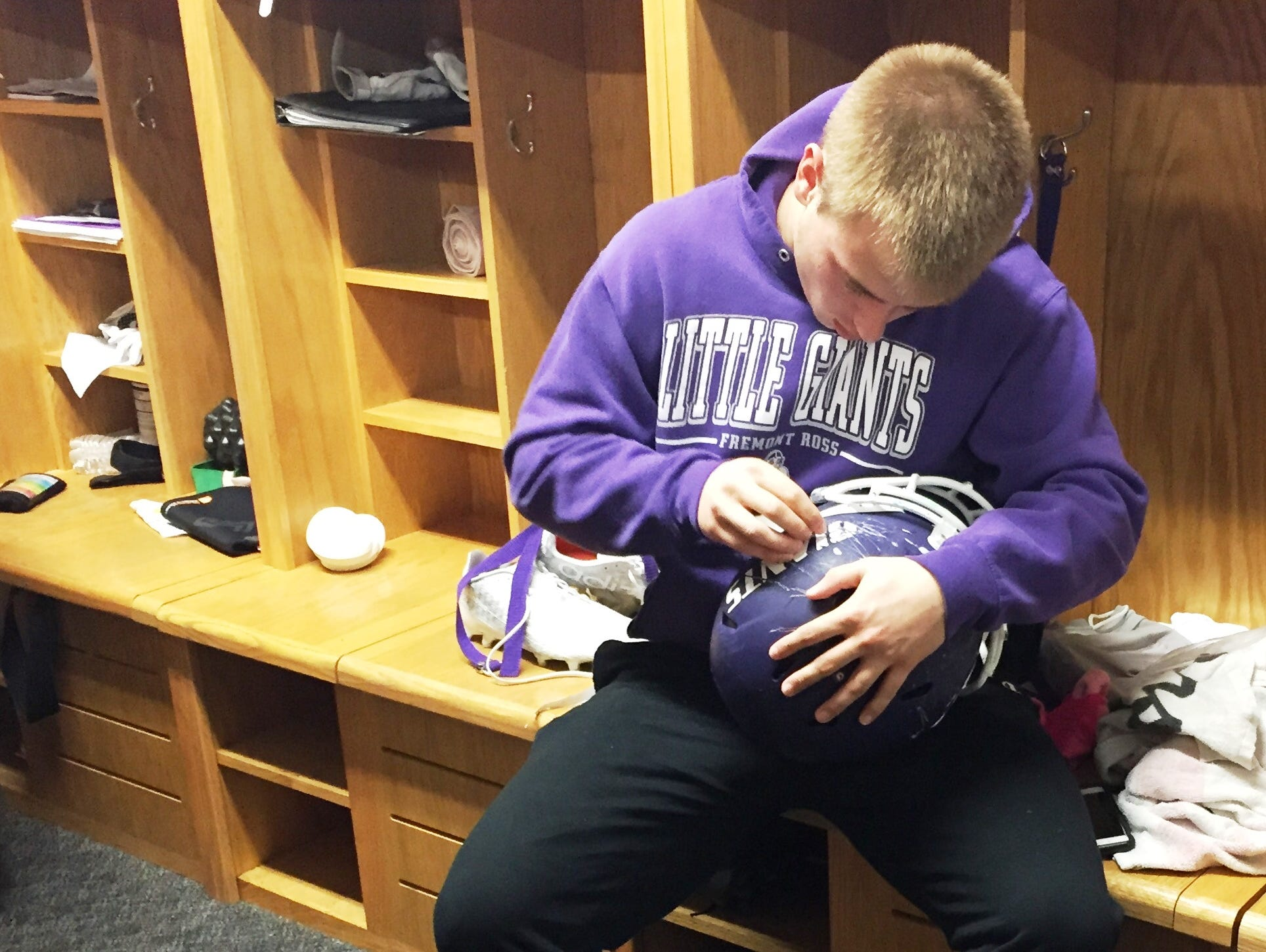 Fremont Ross senior Sam Detwiler sits at his locker stall and peels the stickers from his helmet Monday afternoon.