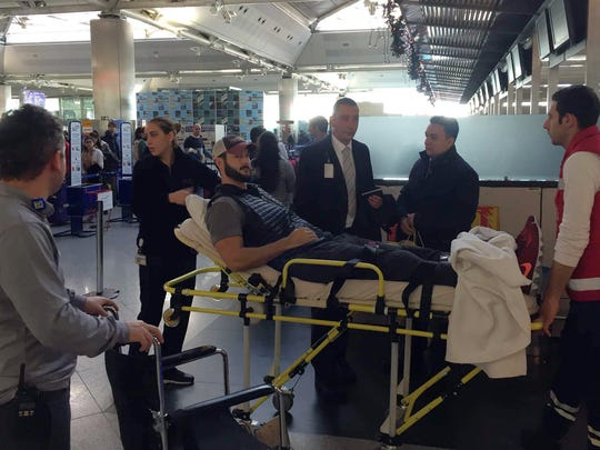 People carry Jake Raak, 35, on a stretcher as he returns back home at Ataturk Airport, in Istanbul, on Jan. 2. Raak had been shot in the leg.