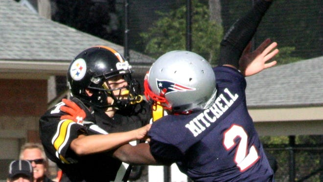Plymouth-Canton Steelers varsity defensive end Liam Radomski applies pressure to the Birmingham Patriots' quarterback Saturday afternoon.