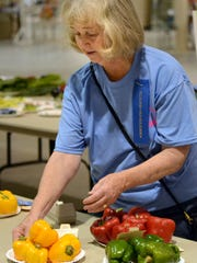 Volunteer Ginger Thiels displays winners of the vegetable competition during the Rapides Parish Fair on Wednesday. The fair opened Wednesday on U.S. Highway 71 near LSUA and runs through Sunday.