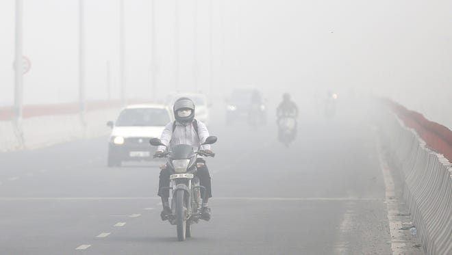 Motorists drive surrounded by smog in New Delhi, India,  Nov. 8, 2017.