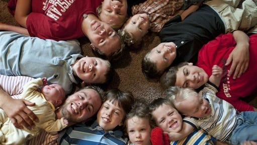In this Aug. 6, 2013 photo, the 12 Schwandt brothers pose for a photograph in their home in Rockford, Mich. Clockwise from bottom left are: Tyler, 21, holding Tucker, 2 days;  Vinny, 10; Drew, 16; Zach, 17; Charlie, 3; Calvin, 8; Brandon, 14; Luke, 19 months; Gabe, 6; Wesley, 5 and Tommy, 11. Parents Jay and Kateri Schwandt are expecting a baby on Saturday, May 9, 2015, a day before Mother's Day, and they're sticking to their tradition of not finding out in advance whether they're having a boy or girl. (Chris Clark/The Grand Rapids Press via AP) ALL LOCAL TELEVISION OUT; LOCAL TELEVISION INTERNET OUT