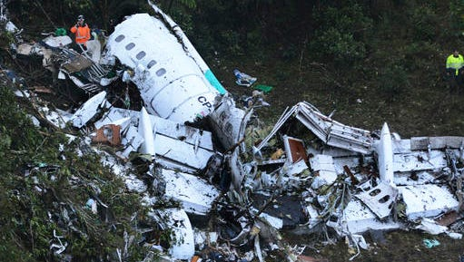 Rescue workers stand at the wreckage site of a chartered airplane that crashed in a mountainous area outside Medellin, Colombia, Tuesday, Nov. 29, 2016. The plane was carrying the Brazilian first division soccer club Chapecoense team that was on it's way for a Copa Sudamericana final match against Colombia's Atletico Nacional.
