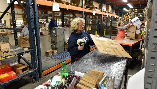 Cindy Parton, center, and Brittany Young, right assemble boxes for shipping at the House-Hasson warehouse in Forks of the River Industrial Park on Jan. 26, 2016.