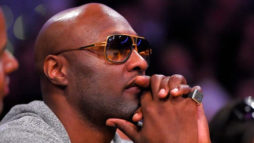 "FILE - In this March 30, 2016, file photo, former Los Angeles Lakers' player Lamar Odom watches during the second half of an NBA basketball game between the Lakers and the Miami Heat in Los Angeles. Odom told Us Weekly for a story published online March 29, 2017, that he is ""a walking miracle"" after being found unconscious with cocaine in his system in a Nevada brothel in 2015."