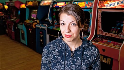 This photo provided by Anita Sarkeesian shows her with vintage video game machines in MInneapolis. Sarkeesian has canceled a speech at Utah State University after learning the school would allow concealed firearms despite an anonymous threat against her. Sarkeesian was scheduled to give a presentation on the portrayal of women in video games Wednesday. She decided to cancel Tuesday after the university received an anonymous threat from a person who threatened to carry out a mass shooting if the event was held. Sarkeesian pulled out after learning from university officials that concealed weapons would be permitted, as long as attendees have a valid concealed firearm permit in accordance with Utah law