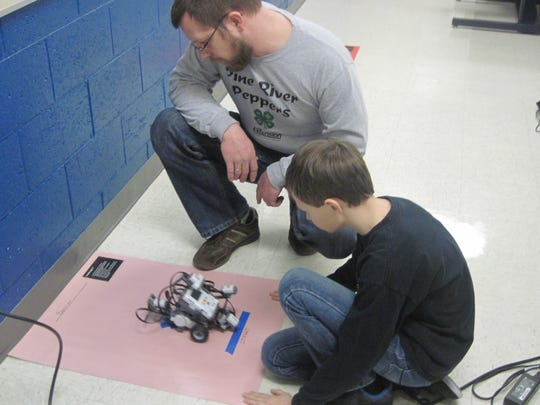 Hunter shows Peter a robot completing a challenge during a robotics session at Project Discovery Day.