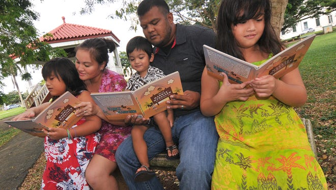 """In this file photo, local athor Christine Restuvog Quinata, second from left, sits with her family as they are photographed reading copies of her published book entitled, """"Meet the Mannge' Manhoben."""" More books like this may appear in libraries and bookstores as a workshop is currently underway to help aspiring authors publish children's books on local culture."""