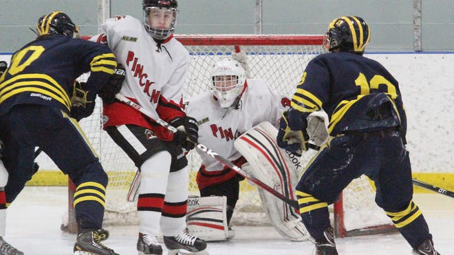 Pinckney's Jake Kestner, center left, and Pirates goalie Nick Lefebvre, center, bear down as Hartland forwards Phil Caris, left, and Blaise DesChamps, right, converge on net. The Eagles extended their win streak to five in a row with a 9-0 win over Pinckney Wednesday night.