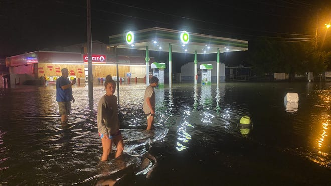 People walk on the flooded Sea Mountain Highway in North Myrtle Beach, S.C. as Isaias neared the Carolinas on Monday night.
